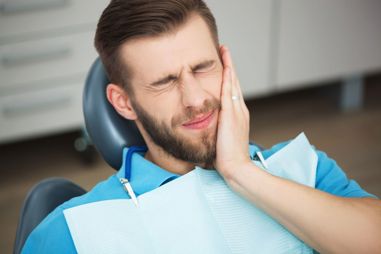 Young-man-with-tooth-pain-sitting-in-a-dentist's-chair.-617773796_4493x2995